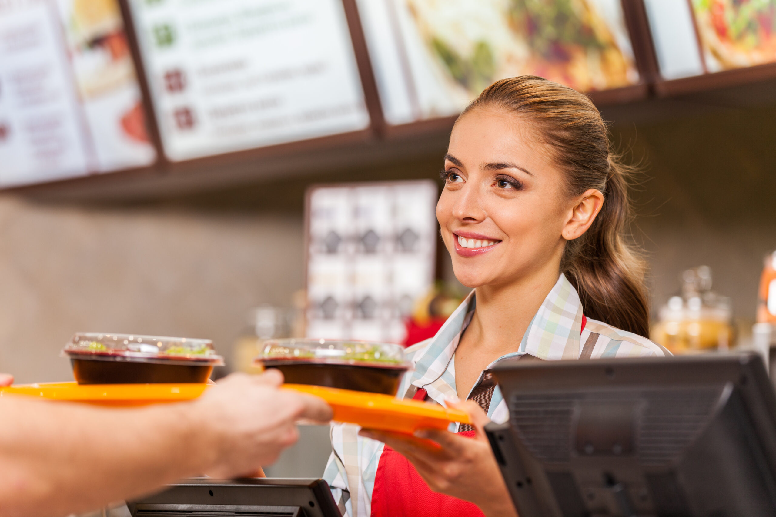 Employee serving two fast food meals