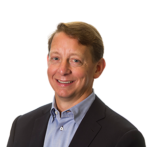 Tim Gruidl, Fishbowl Solutions president, poses for a headshot photo in a black suit against a white backdrop.