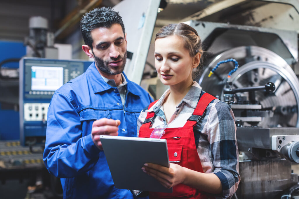 Two manufacturing workers in discussion and looking at tablet computer