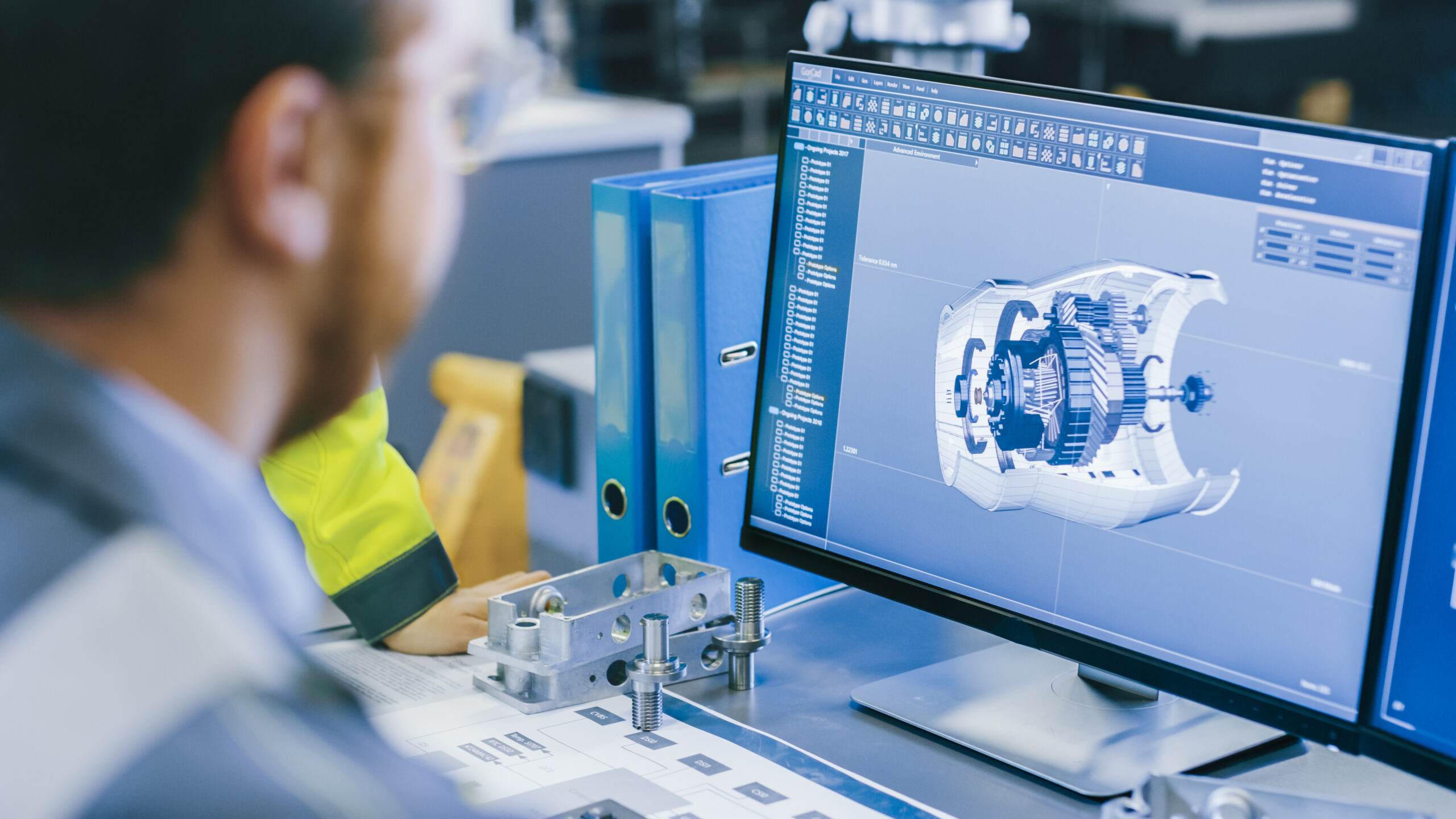 Close-up Back View of a Mechanical Engineer Designing 3D Engine Model on Computer utilizing MBD and MBE technologies. Professional Working At a Factory designing.